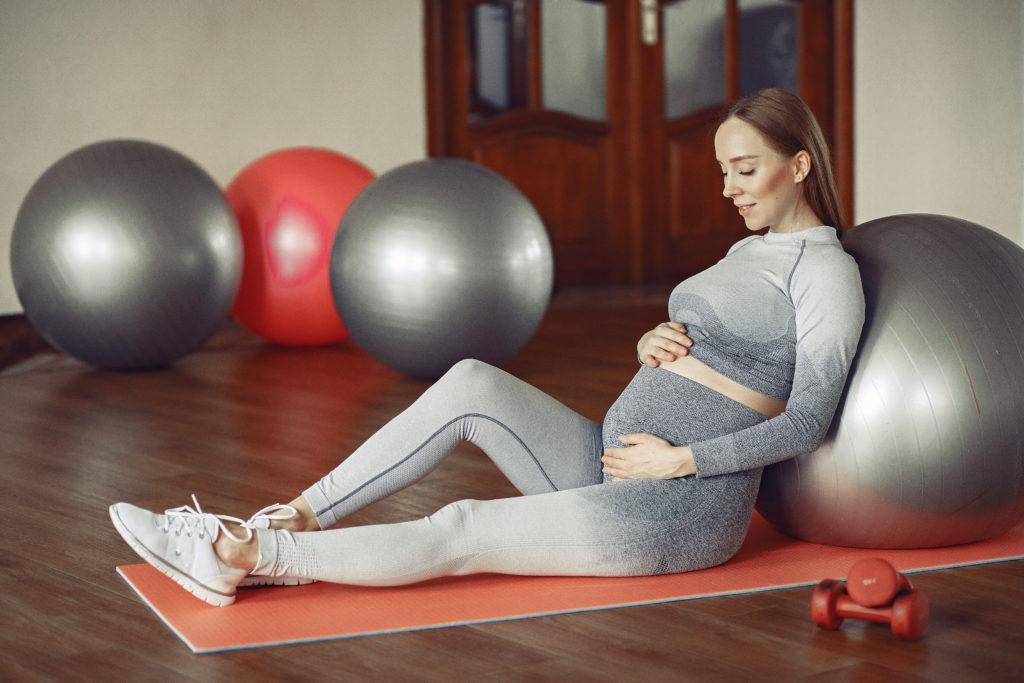 Mujer embarazada haciendo gimnasia con una pelota de yoga para prepararse para el nacimiento de su hijo.