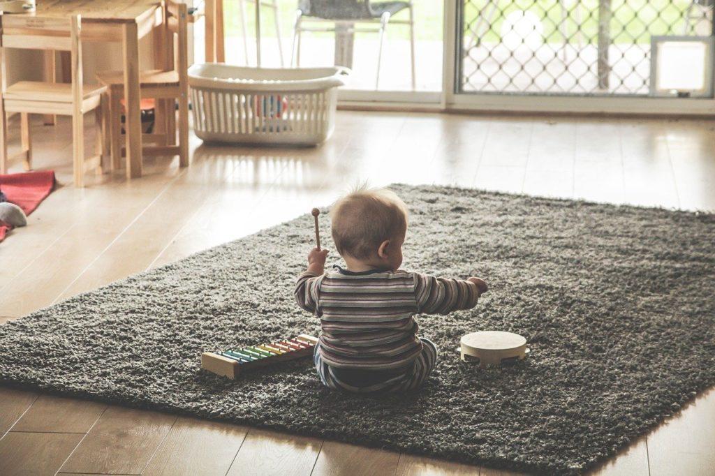 Bebé sentado jugando sobre una alfombra.