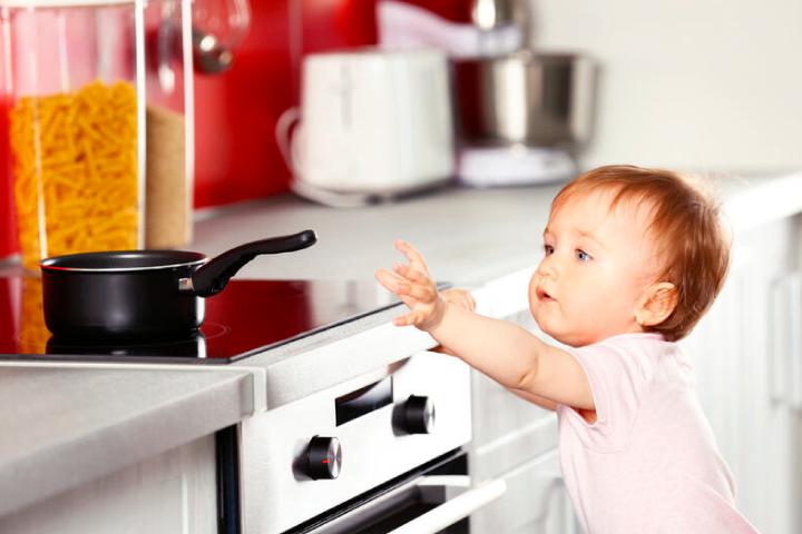 Bebe agarrando olla en la cocina