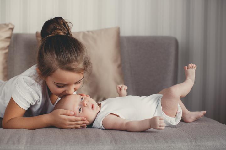 Nena besando a su hermanito nuevo